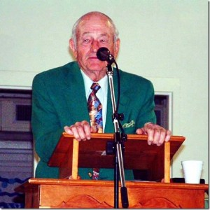 "Photo by Harry West ""Coach"" addressing the RHS Class of 1957's 47th Reunion in March 2004 – called the ""Last Chance Reunion"" as they were to demolish the old Rockingham High School building that summer."