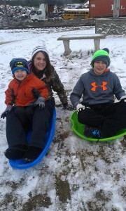 Photo by Jamie Gerald of Benson Starling, Braxton Butler and Brittany Knight sledding at Outreach for Jesus in Hamlet.