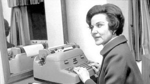 Photo courtesy of Richmond Community Theatre Ann Landers sitting at her desk, hands at the ready of her IBM Selectric electric typewriter for the next advice column.