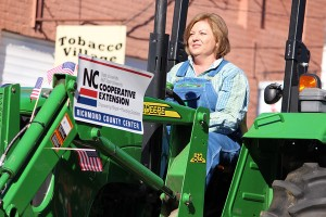 Kevin Spradlin | PeeDeePost.com Susan Kelly, shown here driving a tractor in the 2014 Farmers Day Parade in Ellerbe, presented to the Richmond County commissioners on Monday a grant application for a Green Fields Initiative that will aid local farmers' ability to reach new markets.