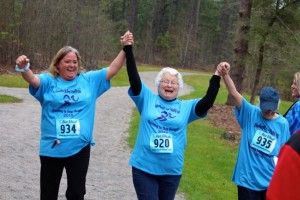 Kevin Spradlin | PeeDeePost.com From left to right, Lisa Benoist, Louise DeBerry and Patsy Hartman raise their arms in triumph as they approach the finish line of the inaugural Hoofing it for Haiti 5K on Saturday at Richmond Community College.