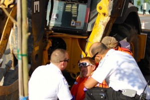 Kevin Spradlin | PeeDeePost.com FirstHealth EMS personnel address the needs of a city of Rockingham employee who was trapped in between the bucket and stick on a backhoe.