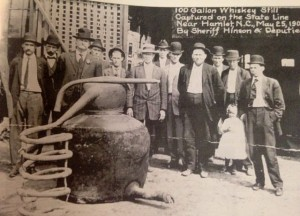 A Richmond County Historical Society photo This photography by Marchant shows a 100-gallon still captured in 1909 near Hamlet. Sheriff M.L. Hinson (third from left) and his deputies found it.