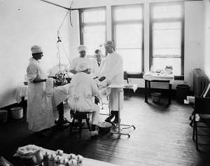 Doctors and nurses operate on a patient at a tonsil and adenoid clinic in Elizabeth City circa May 1922. Image from the State Archives.