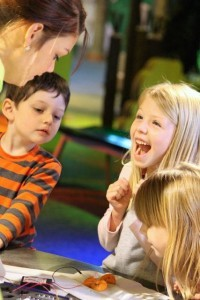 "Kevin Spradlin | PeeDeePost.com Nicole Reidefer, 6, of Raeford, works with Lucas Worley, 4 and sister Hannah Worley, 6, with Discovery Place KIDS staff member Kassie Allen in December during a ""Squishy Circuit"" lab experiment."