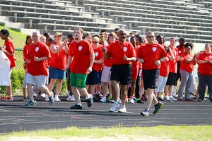 Kevin Spradlin | PeeDeePost.com From left to right, Jason Graham, Special Olympics athlete Daniel Skipper, Richmond County Sheriff James Clemmons Jr. and Sgt. N.L. Forrester complete the 400-meter torch run around the track at Raider Stadium.