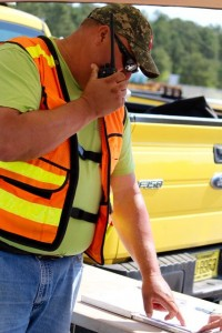 Kevin Spradlin | PeeDeePost.com Jimmy L. Maness, road maintenance supervisor with the N.C. Department of Transportation, reports the score of another driver in the alley dock station on Tuesday at Rockingham Dragway.