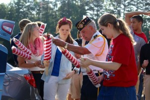 Kevin Spradlin | PeeDeePost.com Retired Army Master Sergeant Jimmy Brigman distributes flags to Temple Christian Academy students on Monday morning at Richmond County Memorial Park.