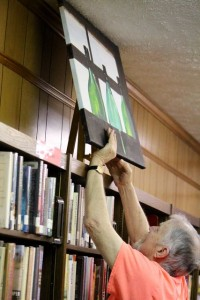 Kevin Spradlin | PeeDeePost.com John Moore, volunteer art class instructor at all three Richmond County senior centers, puts a work of art on display on Friday at the Kemp-Suggs Memorial Library in Ellerbe.