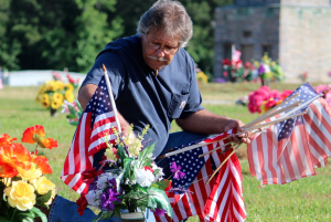 Kevin Spradlin | PeeDeePost.com Randy Von Cannon, of Rockingham, helps plant American flags on veterans' graves at Richmond County Memorial Park.