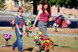 Kevin Spradlin | PeeDeePost.com Shenalyn Hogan, of Derby, and 9-year-old son Michael Flieschman work to put American flags on veterans' gravesites.