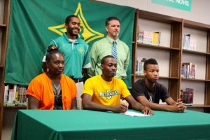 Kevin Spradlin | PeeDeePost.com Erran Greene, sitting (center), is joined by his mother, Tracey Greene, friend Jajuan Graham, Raiders track/defensive backs coach Eric Gould and Athletic Director Ricky Young while signing his letter of intent to run and play football for the Methodist University Monarchs.