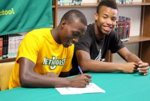 Kevin Spradlin | PeeDeePost.com Erran Greene signs his letter of intent while his friend, Jujuan Graham, shows his support.