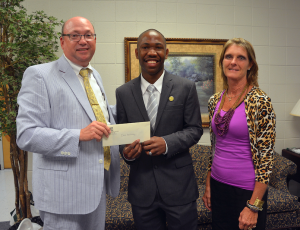 An RCC photo Doni Holloway, a Scotland Early College graduate, won first place in a Richmond Community College essay contest. He is congratulated by RCC President Dr. Dale McInnis and Board of Trustees Chair Claudia Robinette as he accepts his cash prize of $100.