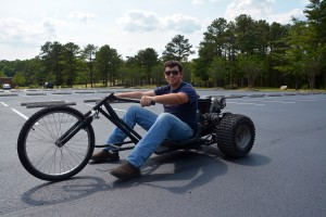 An RCC photo Richmond Community College student Travis Butler sits on the trike that he and his classmate, Jason Felts, built in their welding class. They built the motorized trike using bicycle, lawn mower, go-cart and other scrap parts.