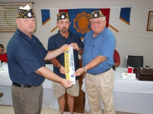Submitted photo N.C. American Legion District 16 commander, Robert L. Steele Sr., left, presents Post 147 commander Wayne Johnson, center; and Phil Bradley, adjutant, with flag streamers recognizing the post's achievement of reaching 100 percent of its membership goal in the past year.