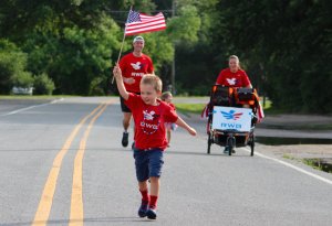 Kevin Spradlin | PeeDeePost.com Eli Erwin raises the flag high at the start of the Team RWB Firecracker 4-mile run Saturday morning in Pinehurst.