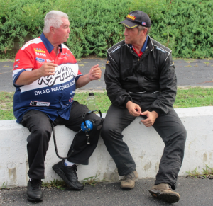 "Submitted photo Sitting on the guardwall at Rockingham Dragway, Pro Stock legend Roy Hill, left, explains the drag racing basics to Mike Rowe, host of CNN's ""Somebody's Gotta Do It."""