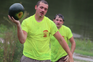 Kevin Spradlin | PeeDeePost.com Dalton Jenkins walks away with a watermelon after battling fellow volunteer firefighters, a couple of hoses and a very slippery course.