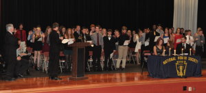 "Photo by Stan Eisel Robert ""Robin"" Godfrey, president of the Mountain Ridge High School chapter of the National Honor Society, leads the 57 inductees in their pledge to formalize membership."