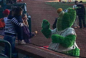 Photo by Kevin Spradlin | PIedmontPostNC.com A young fan takes an extra moment to warm up to Guilford the Grasshopper before the start of Thursday's season-opener against the Hickory Crawdads. Greensboro won, 6-1.