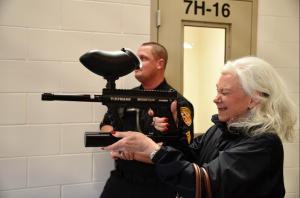 Photo by Kevin Spradlin | PiedmontPostNC.com Citizens Academy member Mary Jo Moody, a retired educator, tries her hand with the pepper ball launcher during a tour of the Guilford County Detention Center in downtown Greensboro. The launcher is a tool, officials explained, to quell unruly inmates without using lethal force.