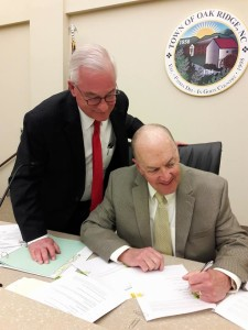 Courtesy photo Oak Ridge Mayor Spencer Sullivan, seated, signs the real estate purchase and sale agreement as Councilman George McClellan looks on with approval.
