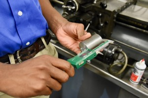 Kevin Spradlin | PiedmontPostNC.com Precise measurements are important for Andrew Hairston, an apprentice at TE Connectivity. Here, he uses an electronic device to ensure accuracy within a certain degree of tolerance.